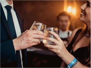 Professioneel geklede man en vrouw klinken met cocktail op privé event