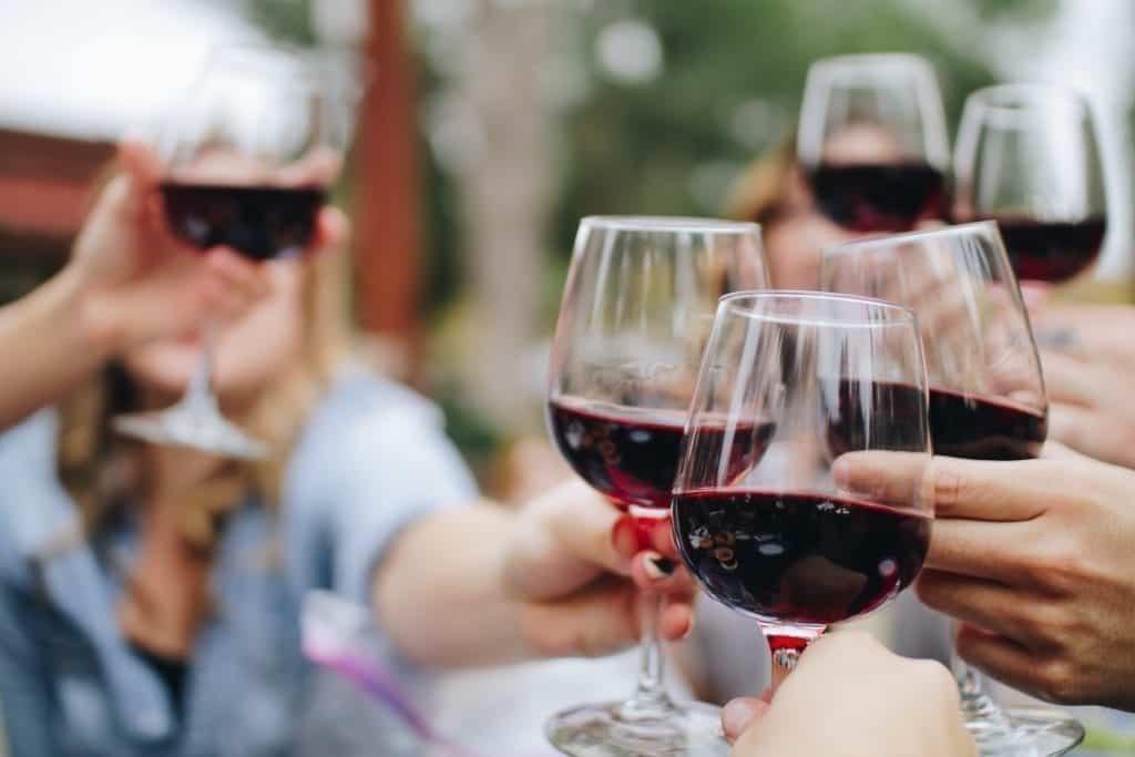 Mensen klinken met glazen rode wijn