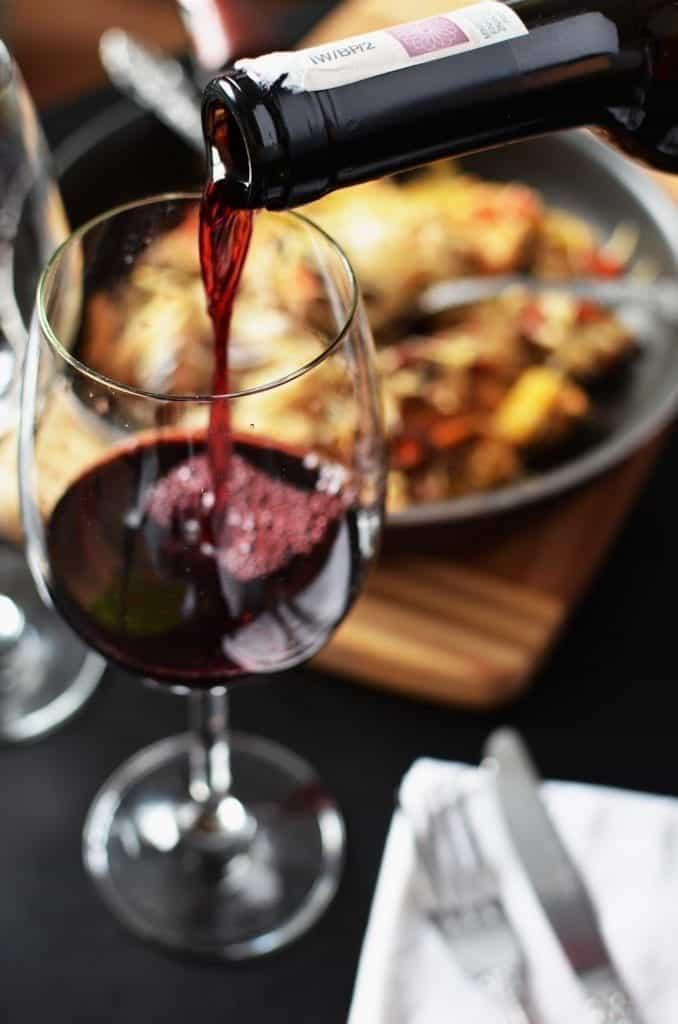 Glas wordt ingeschonken met rode wijn. Op de achtergrond een heerlijk uitziend diner
