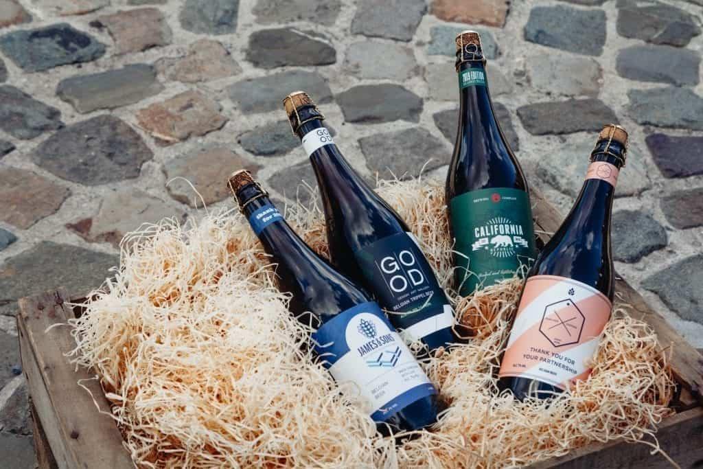 4 verschillende flessen bier met gepersonaliseerde labelen in een kratje hooi