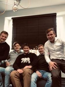 Vijf jonge gasten op sofa kijken naar de camera