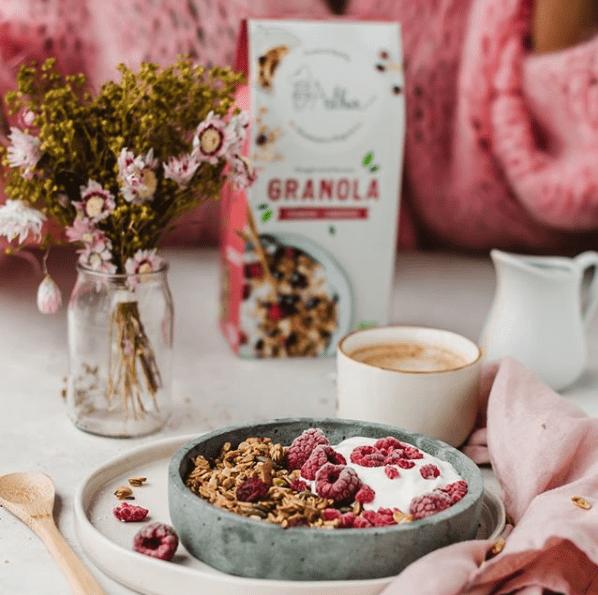een ontbijt met granola, yoghurt, frambozen en koffie en op de achtergrond een vaasje met bloemen